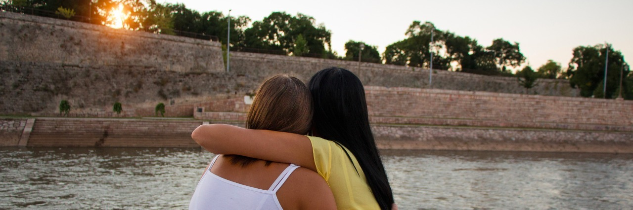 girls hugging each other overlooking a river at sunset