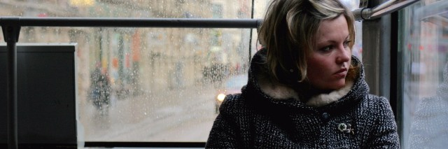woman sitting alone on a bus and looking out the window on a rainy day