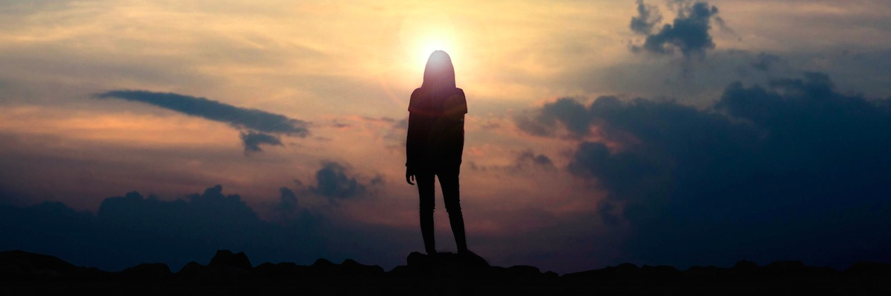 a woman standing on a mountain looking at the sunset
