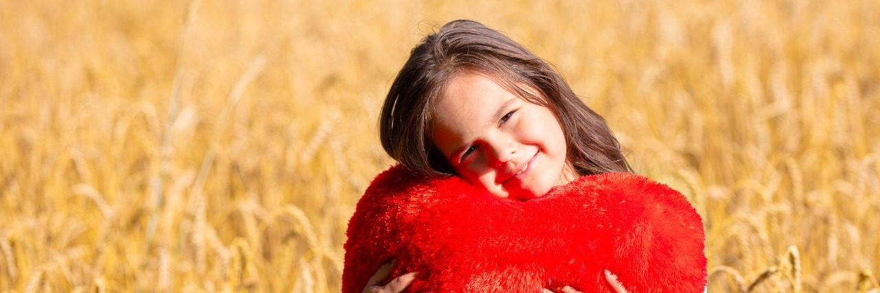 Little girl with heart shaped pillow in the wheat field. Girl cuddling with heart