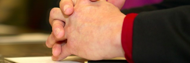 Close-up of folded hands on a table at a meeting