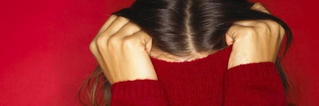 woman hiding under her sweatshirt