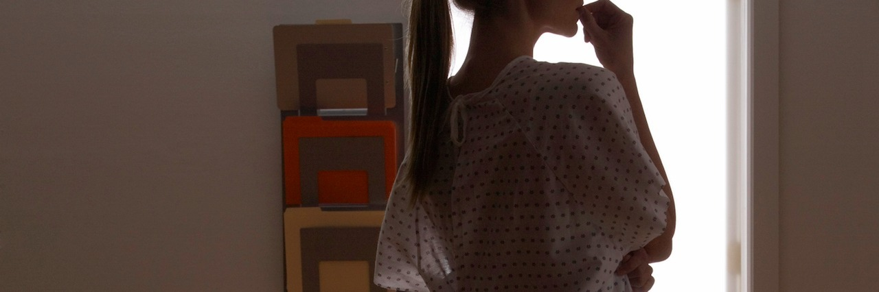 a woman wearing a hospital gown standing in shadows