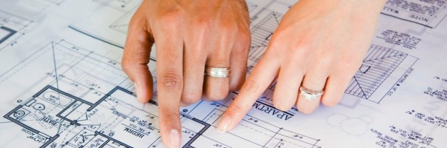 Couple pointing to blueprints