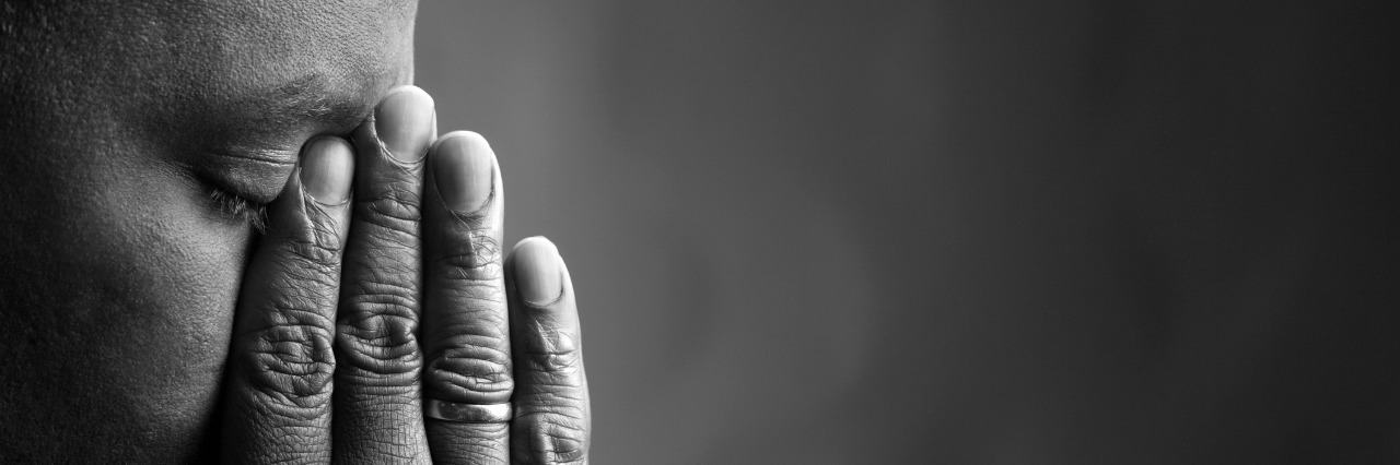 black and white photo of man holding hands over eyes and nose
