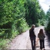 Mother and daughter walking dog on road through forest
