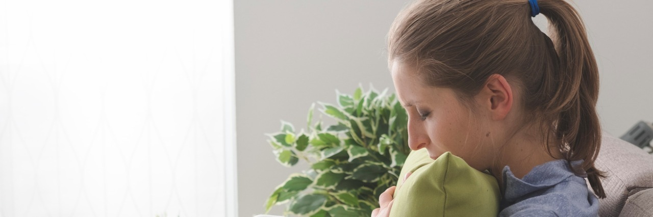 Lonely depressed woman at home, she is sitting on the sofa and hugging a pillow
