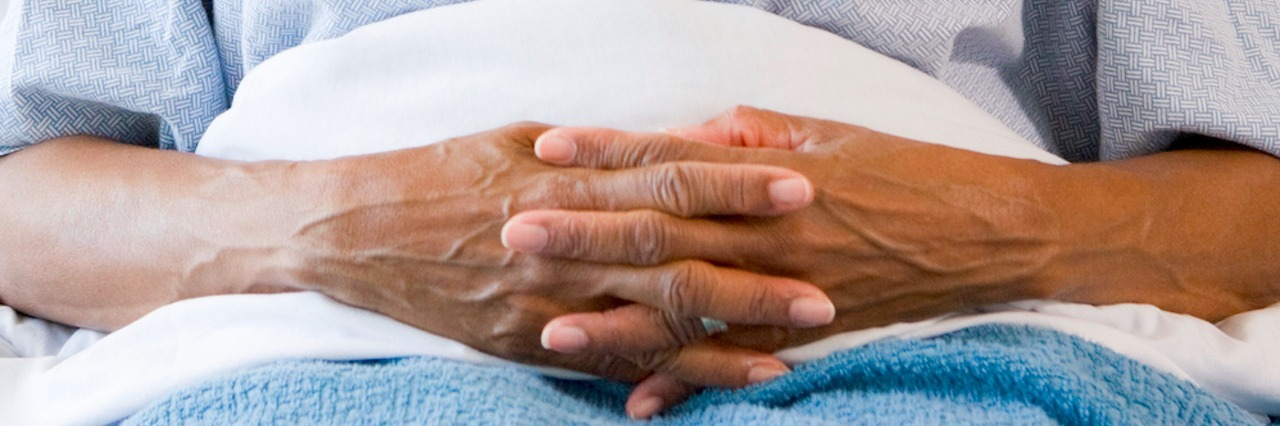 woman sitting in hospital bed with hands folded