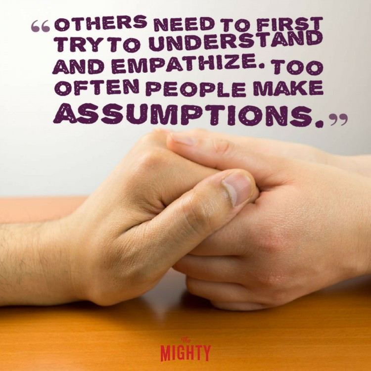 hands holding across table with quote others need to first try to understand and empathize. too often people make assumptions