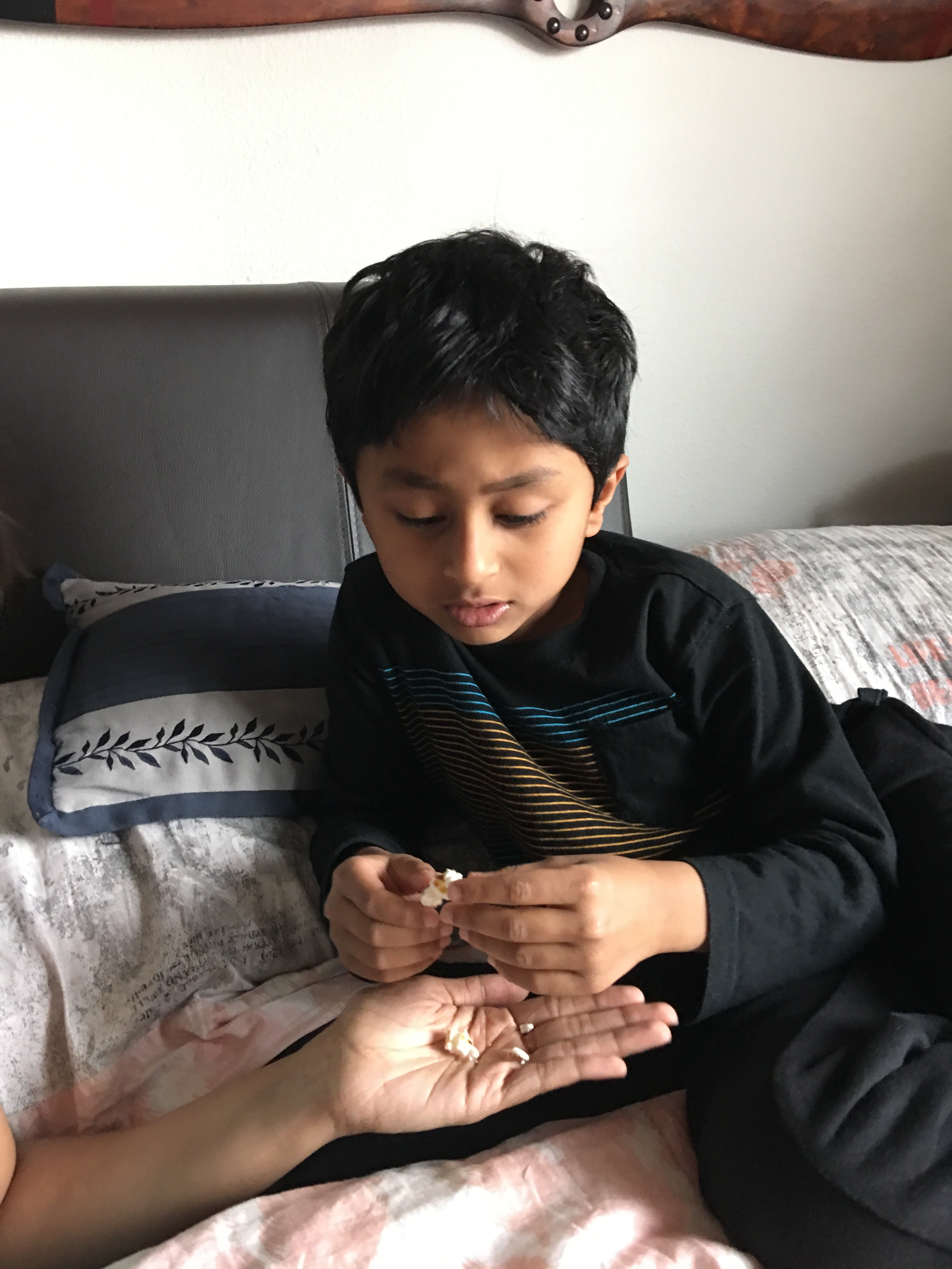 Boy on bed, taking popcorn from someone's hand