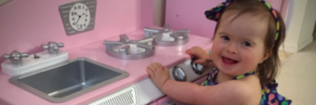 Maria's daughter playing in a pink child's kitchen.