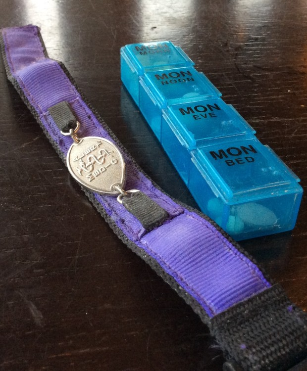 purple keychain with medallion next to blue pill box