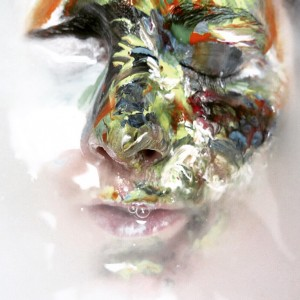 Face with one side covered in paint.