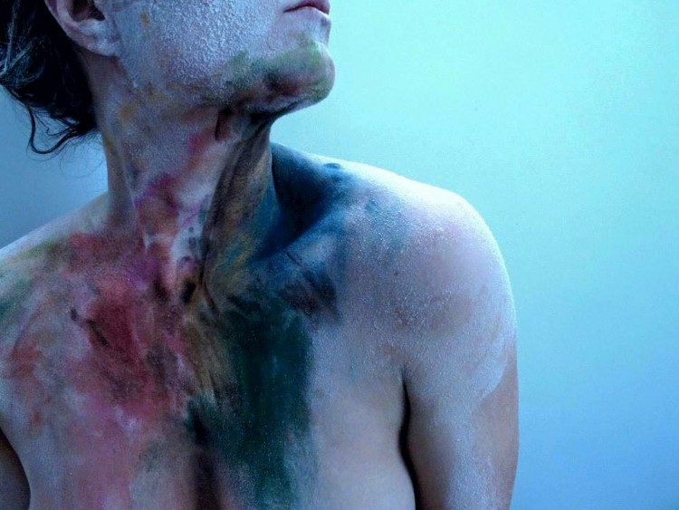Photo of a woman's neck and chest covered in paint. The paint almost looks like bruises.