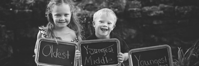 sister and brother holding signs for pregnancy announcement photoshoot