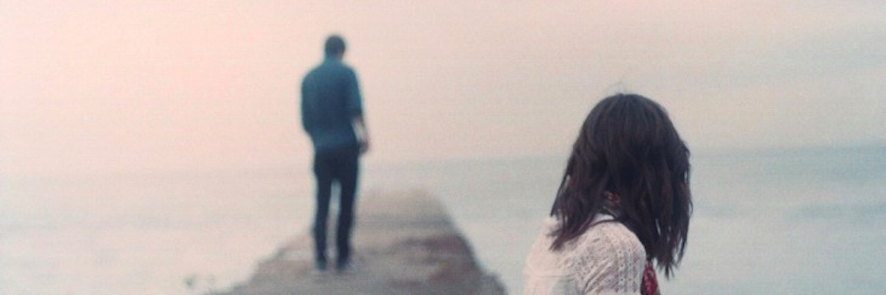 a woman looks at a man standing away from her on a lonely path