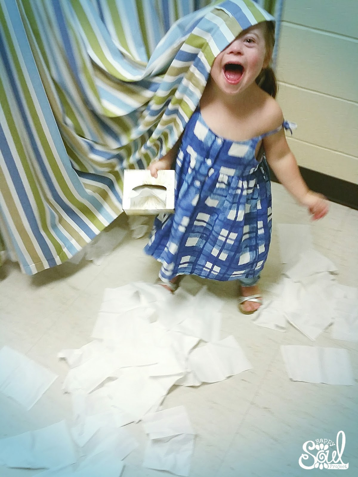 little girl playing with tissues