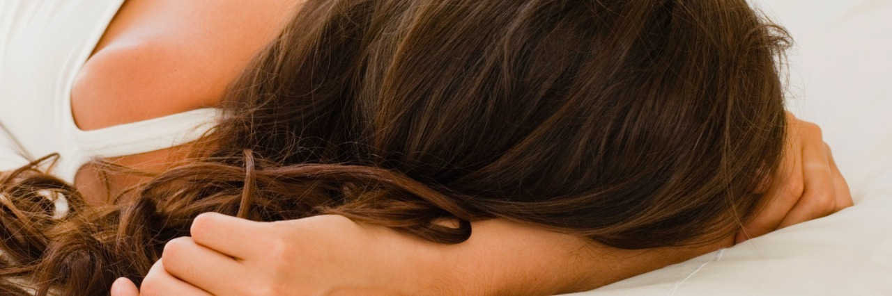 woman lying on bed with head on arm