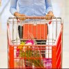 woman pushing cart down supermarket aisle