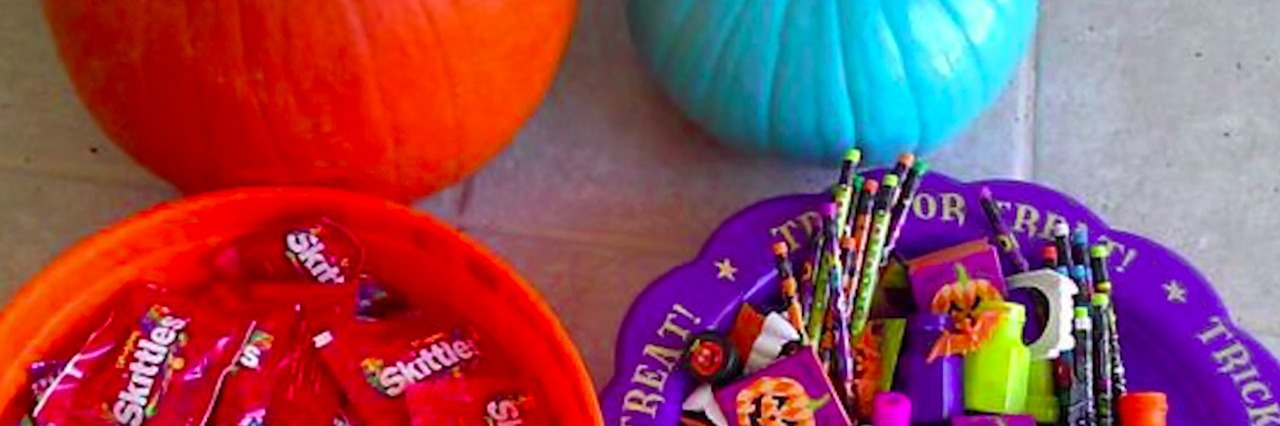 Two bowls of Halloween treats, one filled with candy and the other filled with Halloween-themed toys, in front of an orange pumpkin and a teal pumpkin