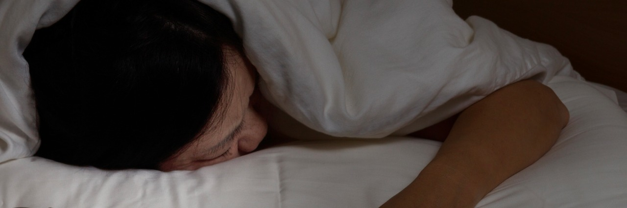 woman sleeping face down with hand outside blanket