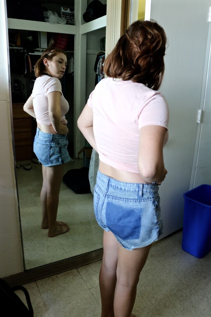 woman looking at her profile in the mirror