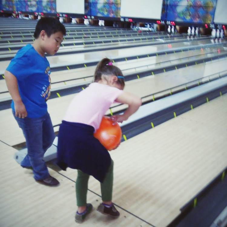 young boy and girl bowling
