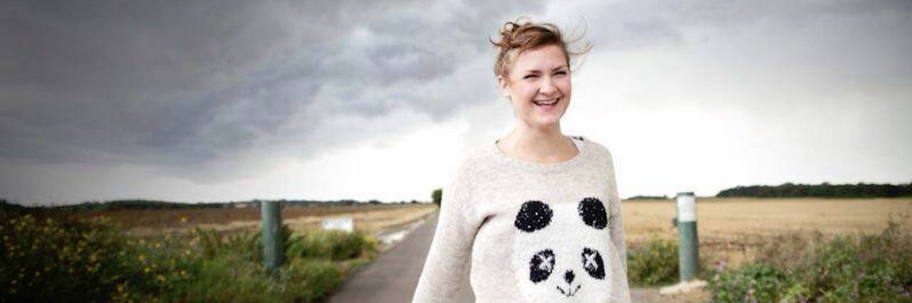 woman wearing a panda sweater walks down a road with dark storm clouds behind her