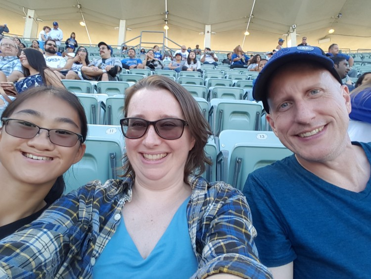 man, woman and child smiling from their seats at a baseball game