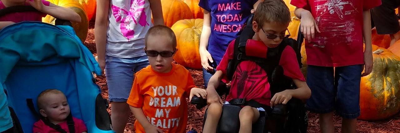 a group of children some with special needs in a pumpkin patch with a service dog