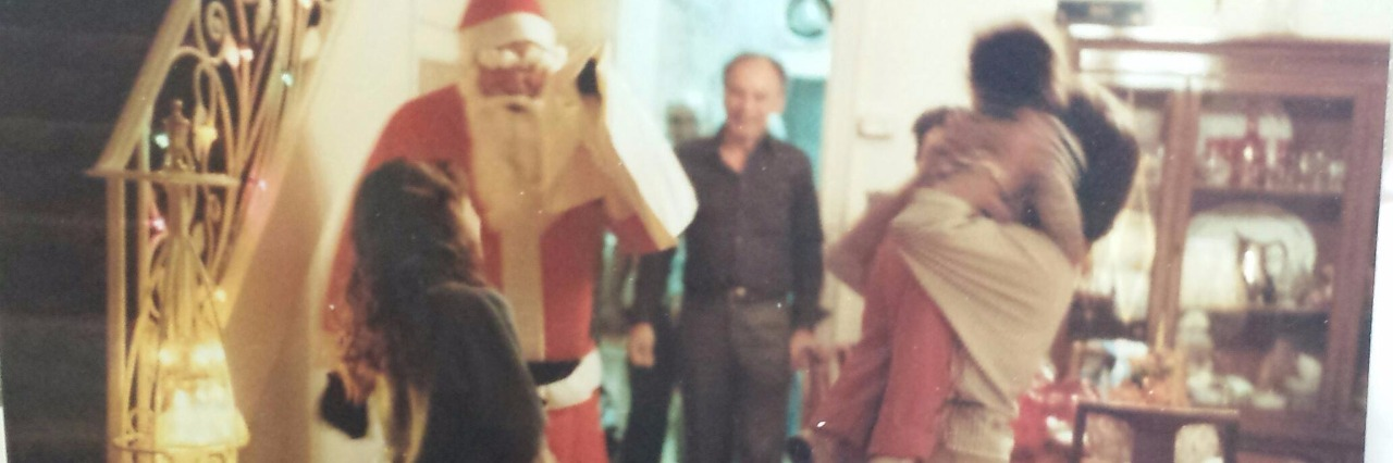 Family holiday gathering at home with person dressed as Santa