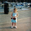 young girl holding toy standing on dock