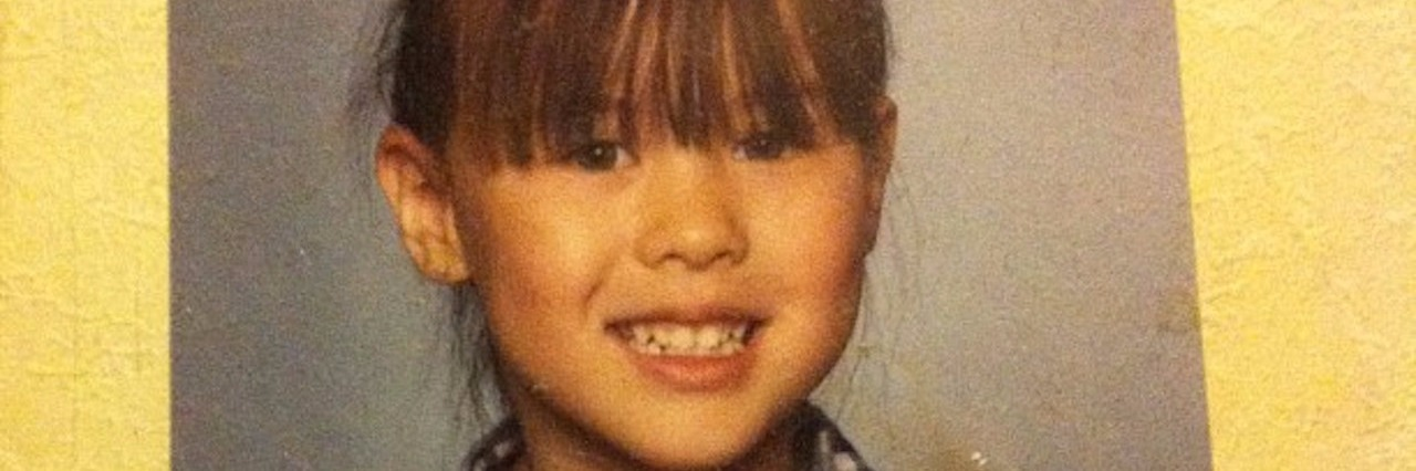 school photo of young girl with bangs and plaid shirt
