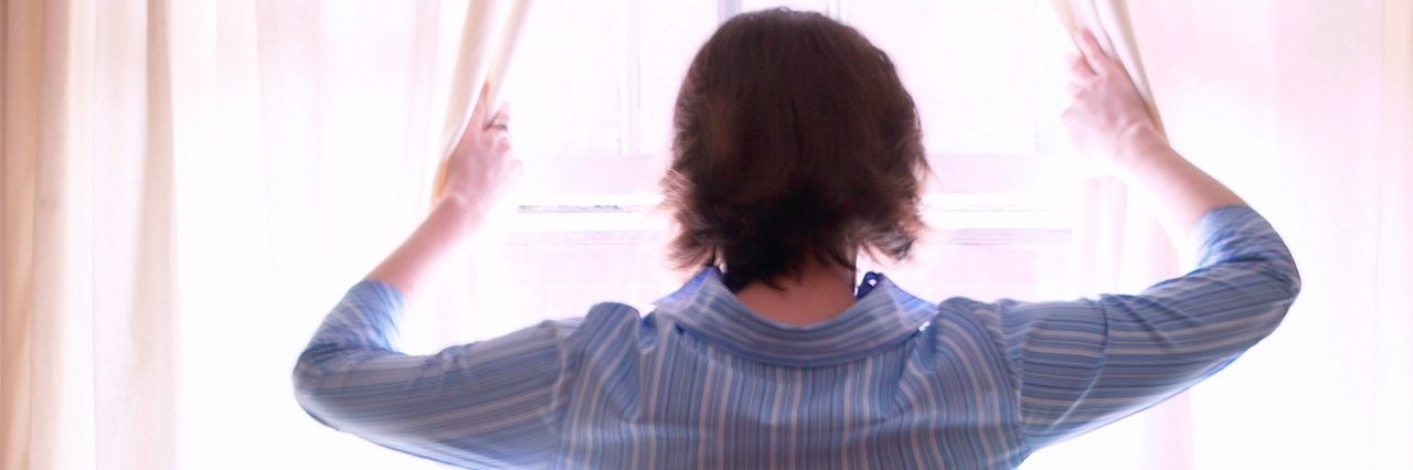 woman opens curtains as she looks out a window