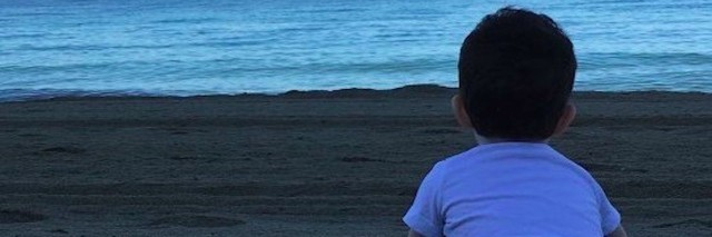 boy on the beach stares at the ocean