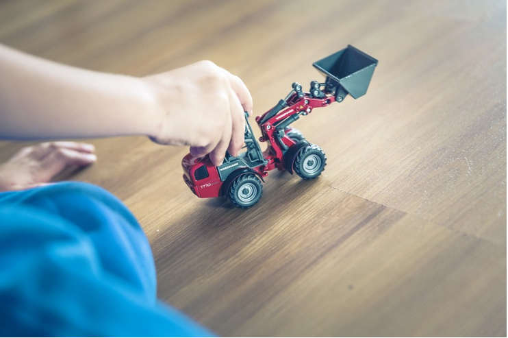 A hand playing with a small toy truck