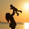 Woman standing on beach at sunrise holding her baby over her head