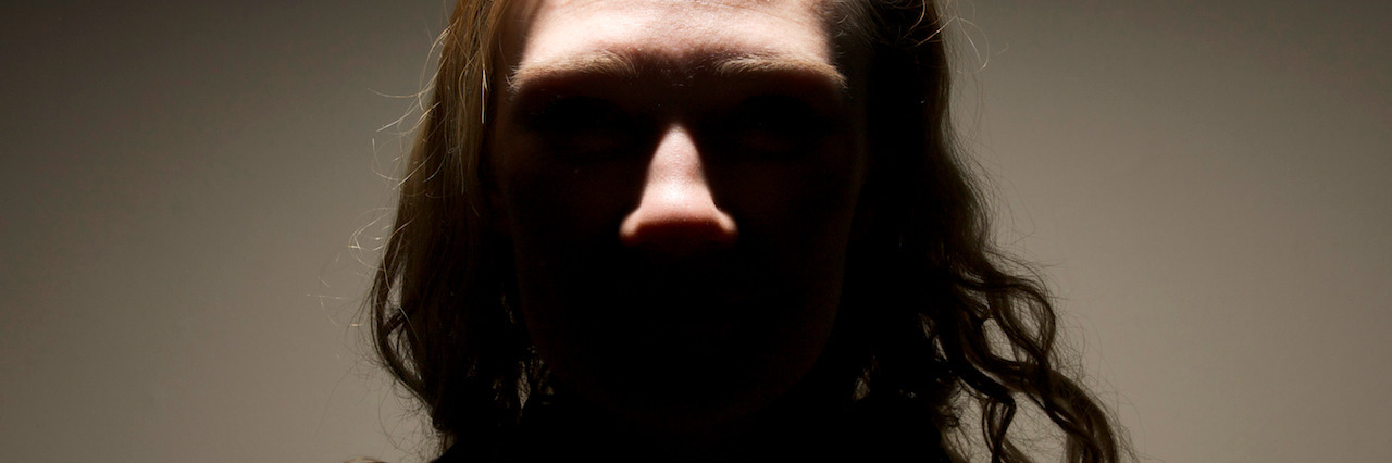 A sinister looking girl, with king-pin villain lighting. Eyes not visible, silhouette of her shape with muted colours and plain background.