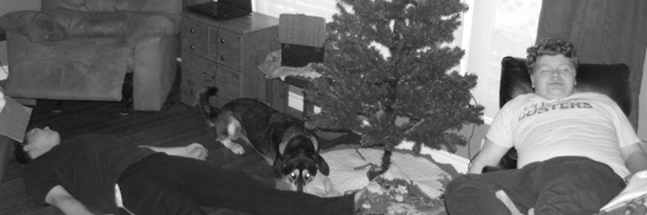 two boys and a dog taking a nap in the living room by the christmas tree