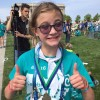 girl wearing a medal and giving a thumbs up