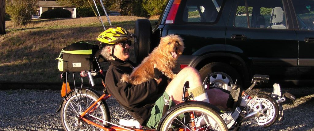 man sitting on recumbent bike with dog on lap