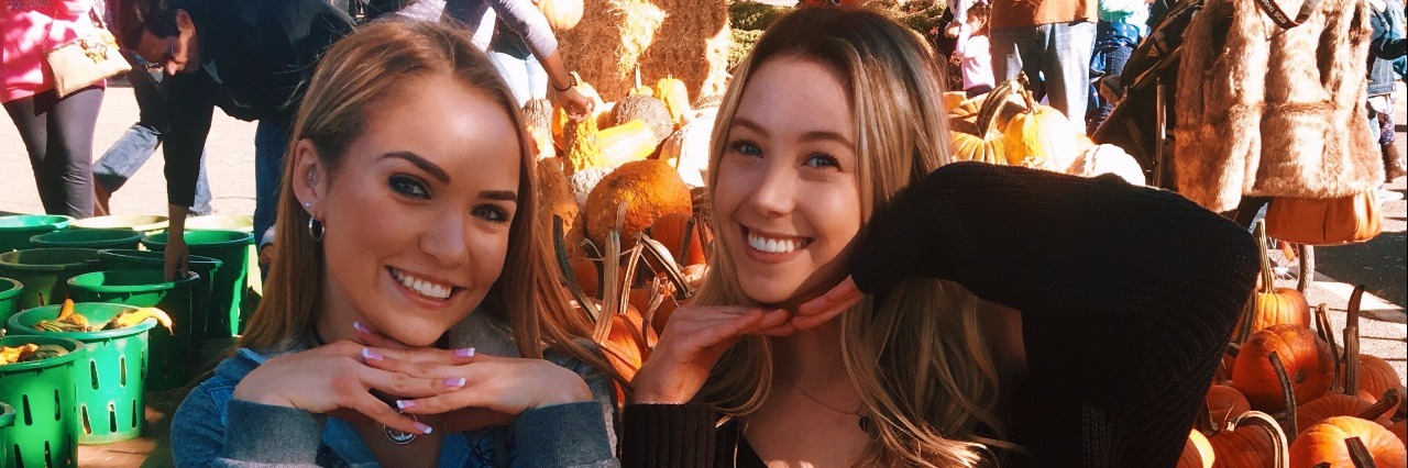 two women holding pumpkins on their laps