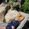 woman laying on lounge chair with hat over face