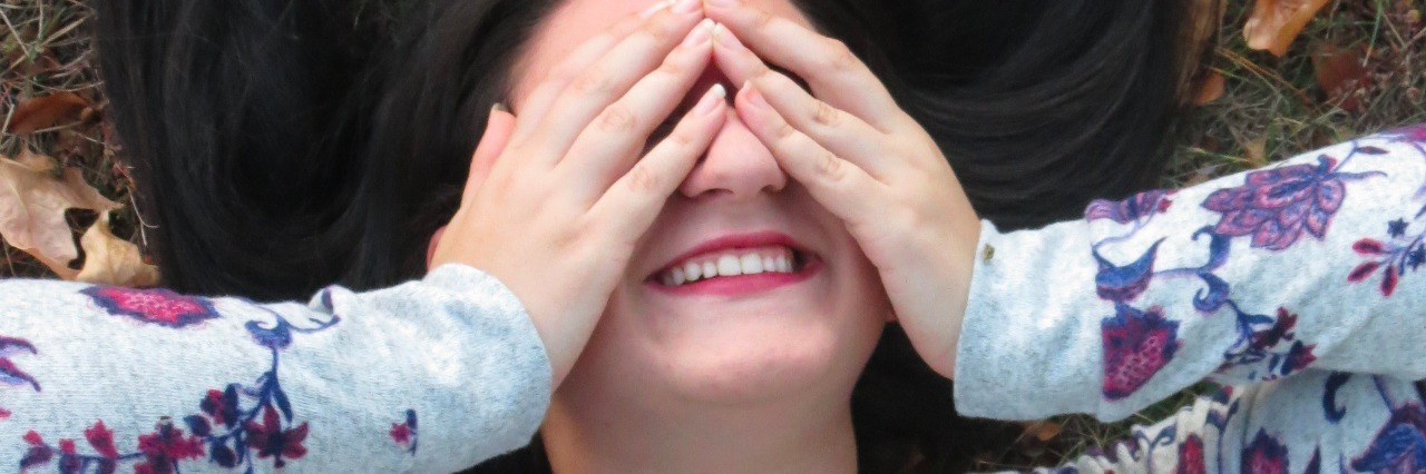 woman holding hands over her face while smiling