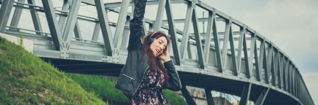 woman wearing headphones dancing near a bridge