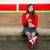 A young girl sitting on the edge of a sidewalk sipping a slurpee