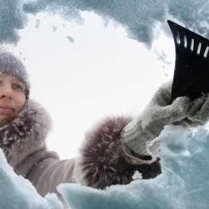woman cleaning snow-covered car with a scraper