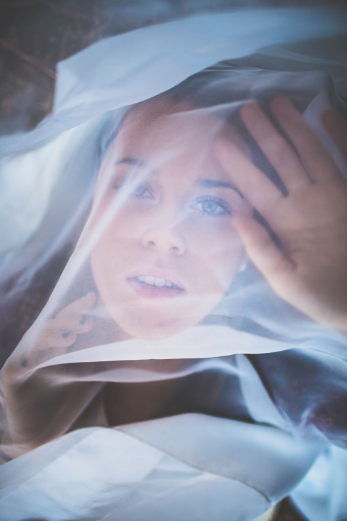 woman looking through sheer white fabric