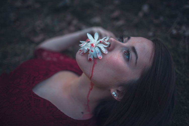 girl laying back with plant dripping with red paint on mouth