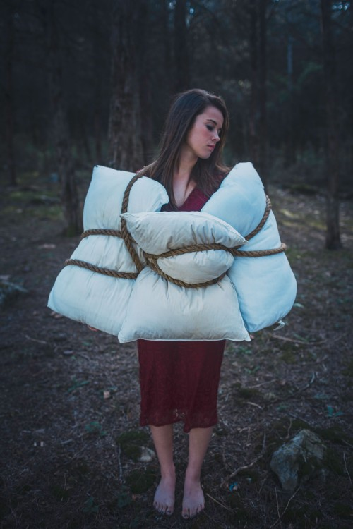 woman standing with pillows tied around her